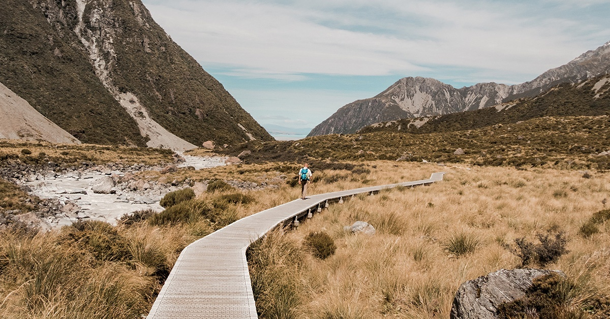 Man walking on platform through mountains