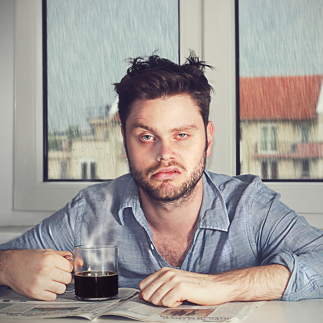 Tired guy in blue shirt drinking coffee reading paper