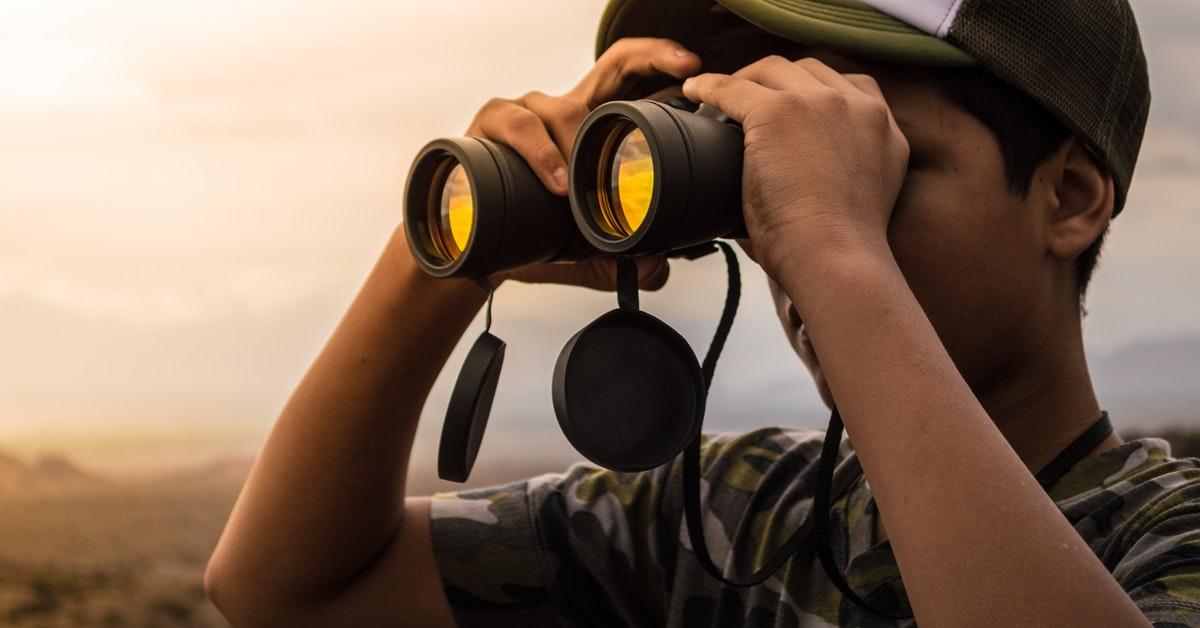 man looking in binoculars during sunset