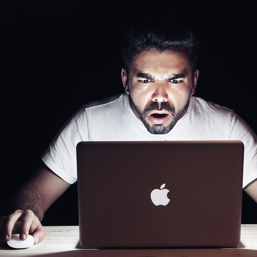 Man on Computer Reading Fake News