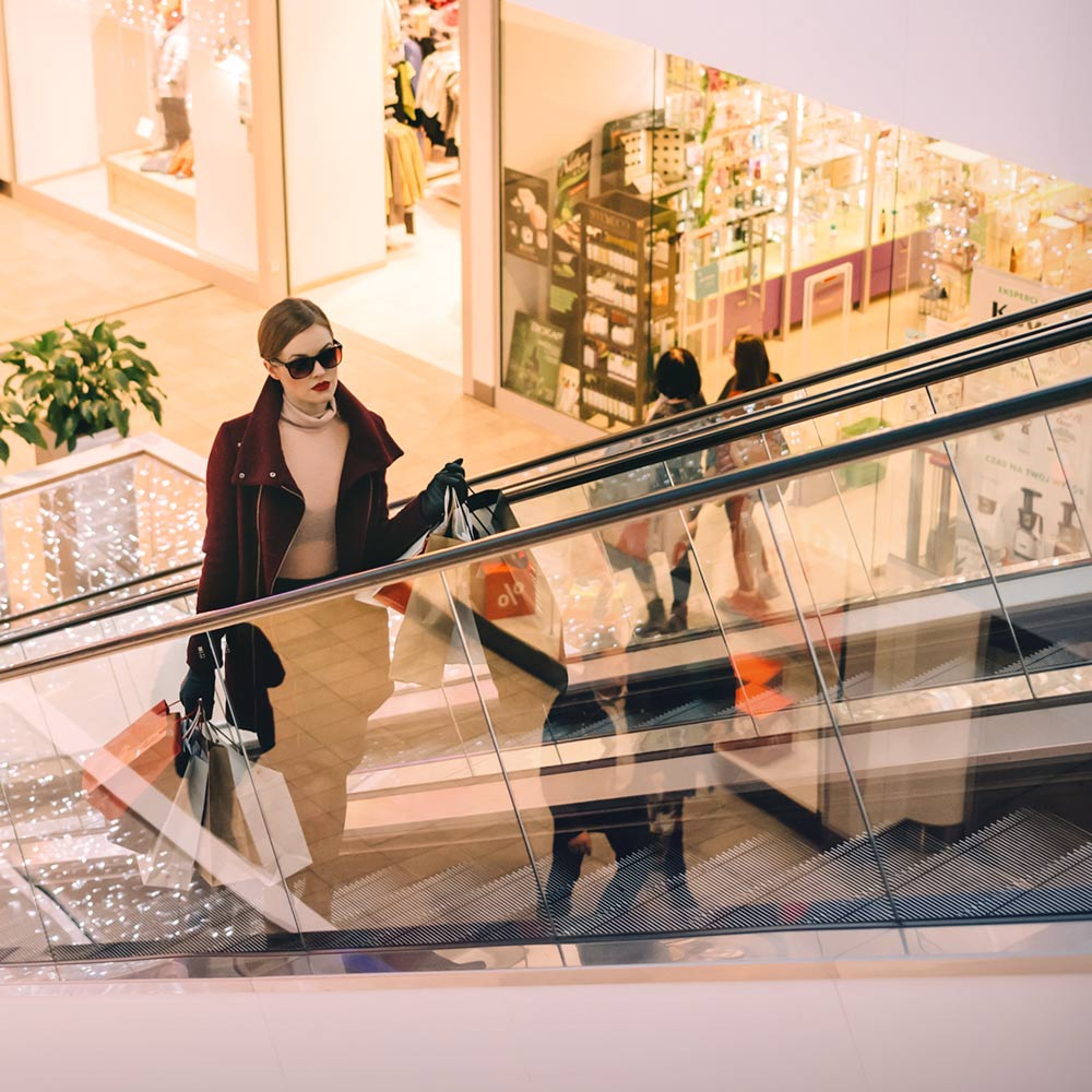 Nicely dressed woman in the mall riding an escalator